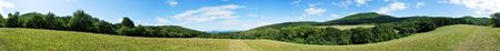 Stitched 360 Panorama of meadows and forest under blue sky