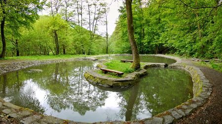 Two benches on the island in the middle of a small lake situated in a quiet park Stock Photo - 7818809