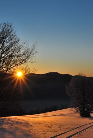 Winter scenery of the sun rising behind the mountain ridge photo