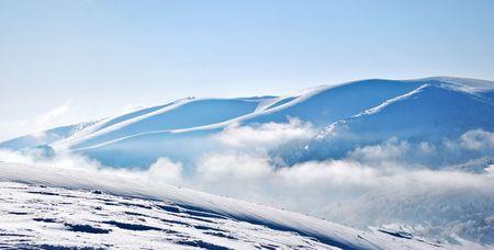 Panoramablick auf verschneiten Bergkämme aus Wolken
