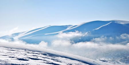 Panoramic view of snowy mountain ridges emerging from clouds