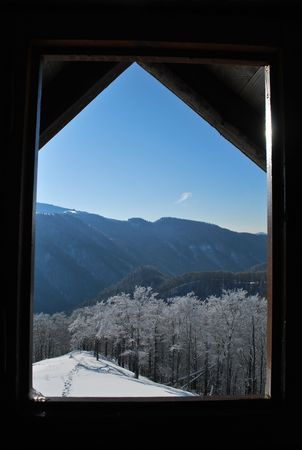 Wooden window view of the winter mountain landscape photo