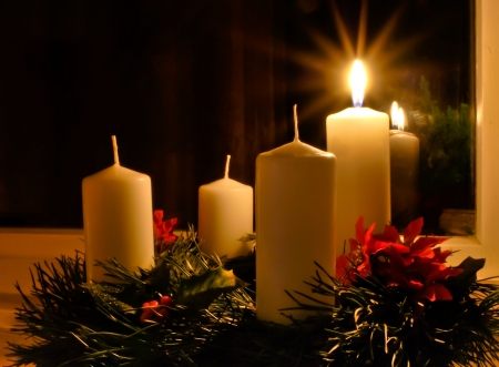 the advent wreath: Corona de Adviento con un cirio encendido que se coloca en la ventana