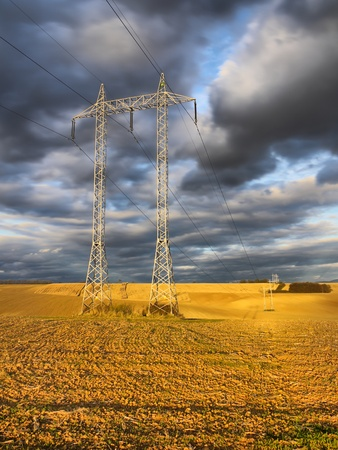 Gloomy clouds above the transmission tower situated in the field Stock Photo