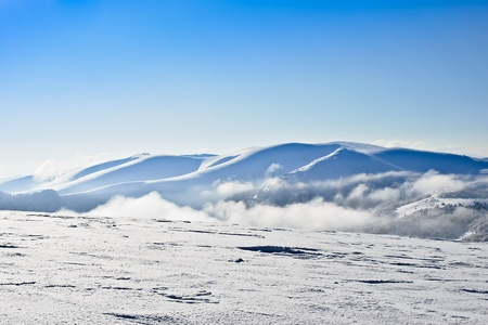 Clear blue sky above the mountain range emerging from clouds Stock Photo