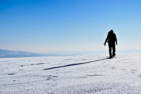 Silhouette and shadow of hiker running on snowy mountain ridge Stock Photo