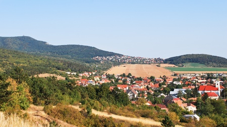 Picturesque modern village under a wooded hill Stock Photo - 8476903