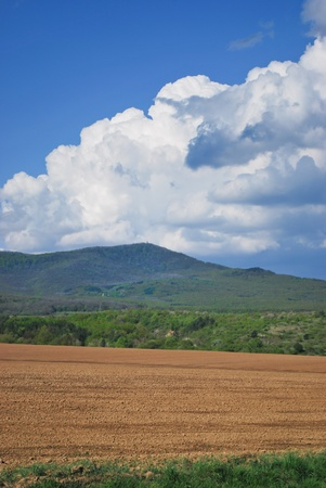 Freshly cultivated soil situated at the foot of a mountain photo