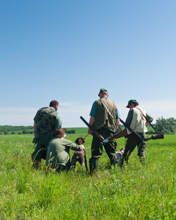 group of hunters with their dogs looking into the distance Stock Photo
