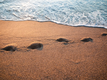 sea water flooded the human footprint on the beach photo