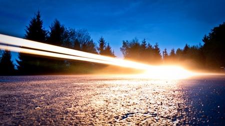 Captured Schein der Autoscheinwerfer, die auf der Straße, die durch den Wald Lizenzfreie Bilder