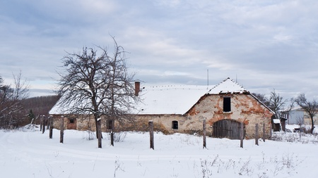 Abandoned farm house in the middle of a snowy landscape photo