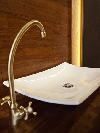 White sink with golden basin mixer and wooden background photo