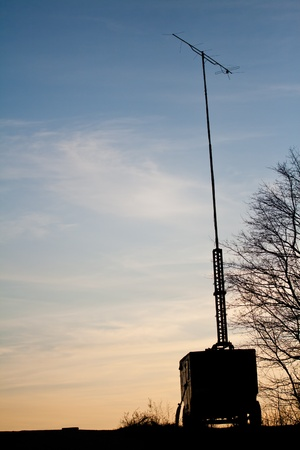 Silhouette of the old mobile transmitter with sunset background photo