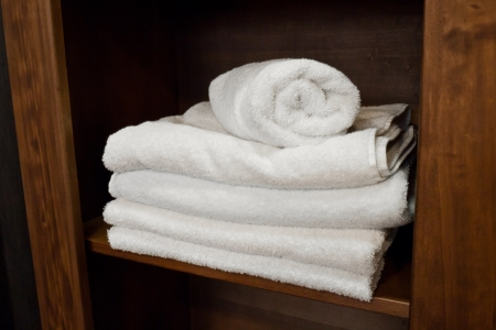 White bath towels placed on bathroom shelf photo