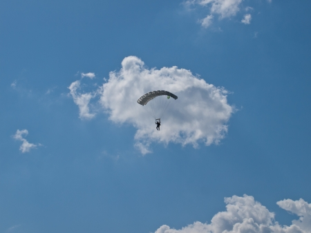 Silhouette of skydiver on blue sky with clouds on background photo