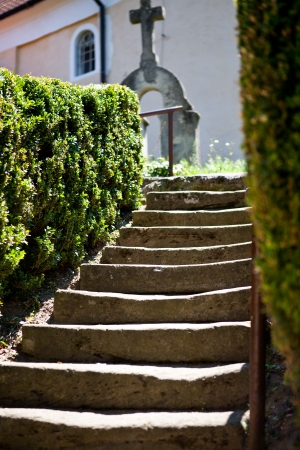 Stairs leading to the church among ornamental shrubs and old graves photo