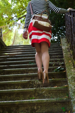 Pin up dressed girl walking up stairs photo