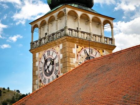 Church tower with a clock and tiled roof
