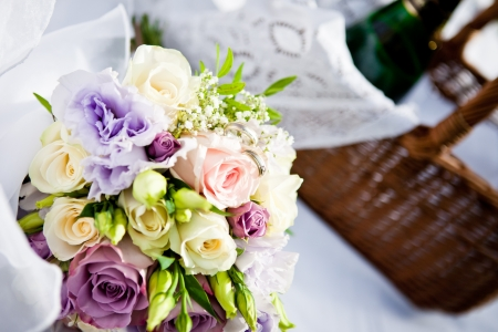 flower arrangement: Close view of a beautiful bouquet of flowers with rings and picnic basket Stock Photo