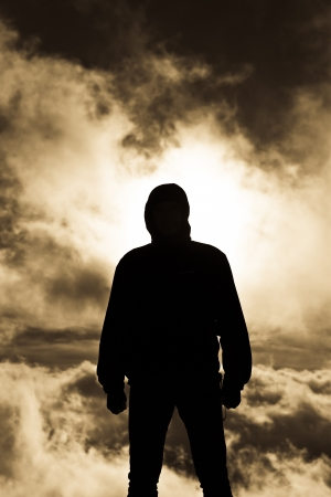 Persistent man silhouette with gloomy clouds as background Stock Photo - 17497834