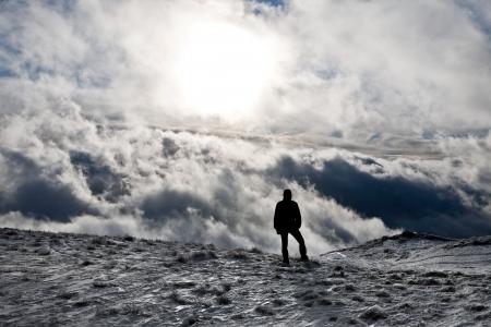 Silhouette eines Mannes, der auf einem Hügel mit dramatischen Wolken als Hintergrund