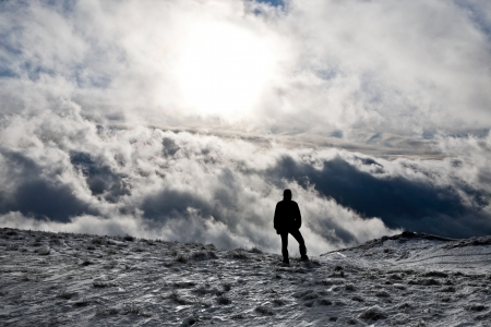 Silhouette of a man standing on top of a hill with dramatic clouds as background