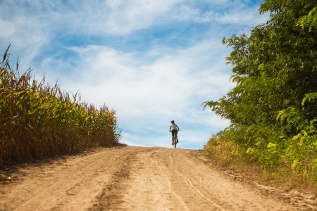 Woman riding a mountain bike on a dirt road photo