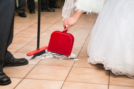 Bride and groom sweep up the pieces of happiness