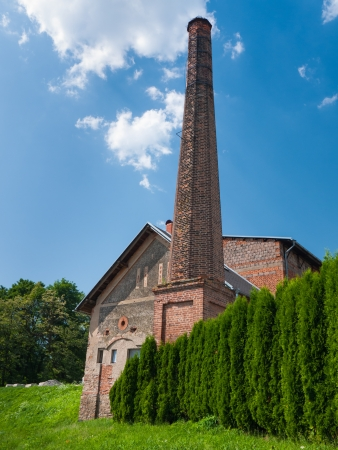 tall chimney: Old brick building of distillery with a tall chimney