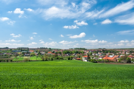 rustical: Rural landscape with lush green wheat with typical European village in the background Stock Photo