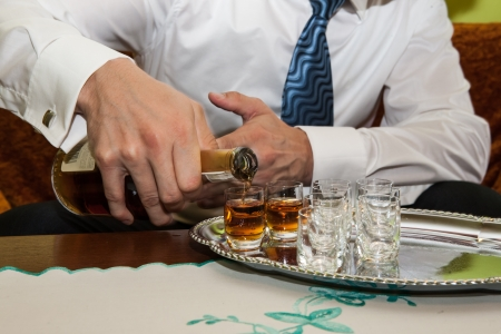 fill up: Man is filling glasses of whiskey in celebration