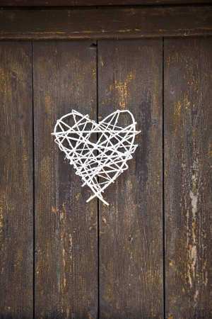 Wicker heart on old wooden door background photo