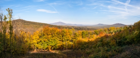 Beautiful autumn forest panorama with distant hills and castle ruin