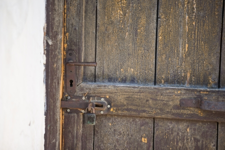 locked up: Old weathered wooden door locked with padlock