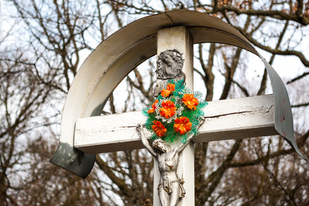 Wooden cross with crucified Jesus and artificial flowers