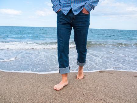 Man in jeans walking along the coast photo