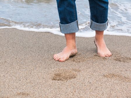 Detail of male feet at the beach with a wave of foaming water