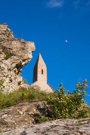 double cross: Vecchia chiesa di San Michele contro il cielo blu con la luna