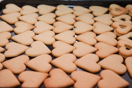 Freshly baked heart shaped cookies on a baking tray photo