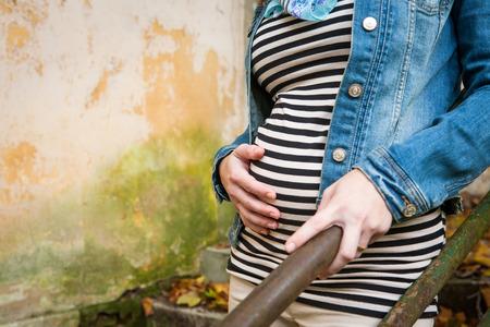Junge schwangere Frau, die auf Treppen umarmt ihre Hand auf ihren Bauch