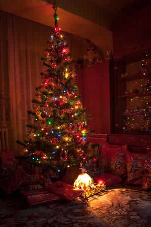 beautiful jesus: Gifts a glowing wooden bethlehem nativity under beautiful decorated and shining Christmas tree Stock Photo
