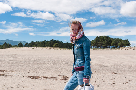 Young beautiful woman in jeans clothes passing through sandy beach photo