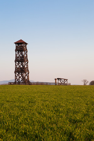lookout: lookout tower in the green field with blue sky