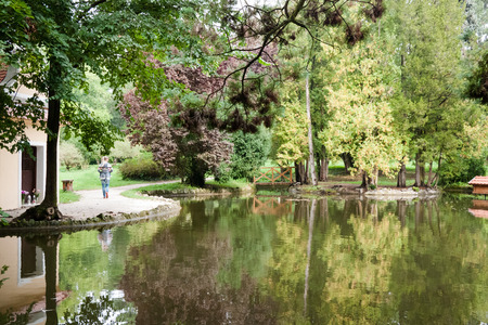 walk in: Woman on a walk around the garden pond in tree park Stock Photo