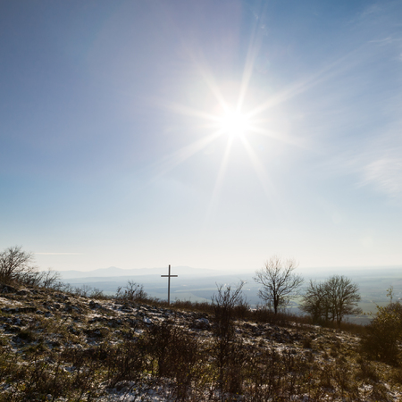 ravaged: Sunshine over the Christian cross in ravaged country Stock Photo