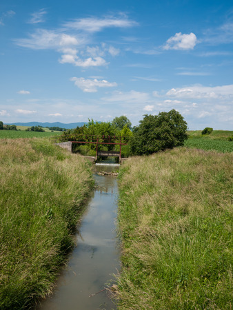 Irrigation canal with open sluice and flowing water