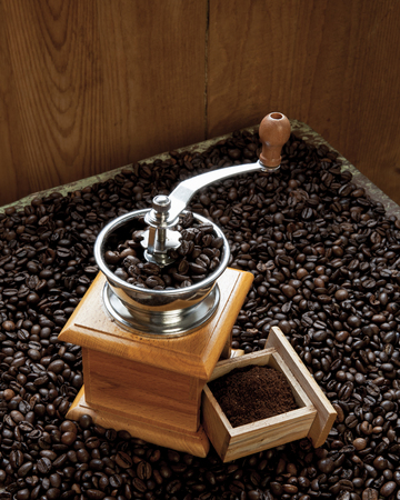 grinded: Coffee grinder and fresh grinded coffee beans on wooden background Stock Photo