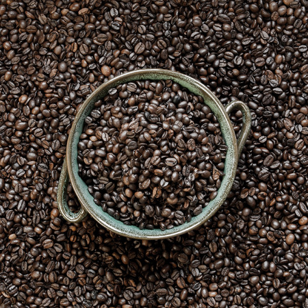 Roasted coffee beans and ceramic bowl background