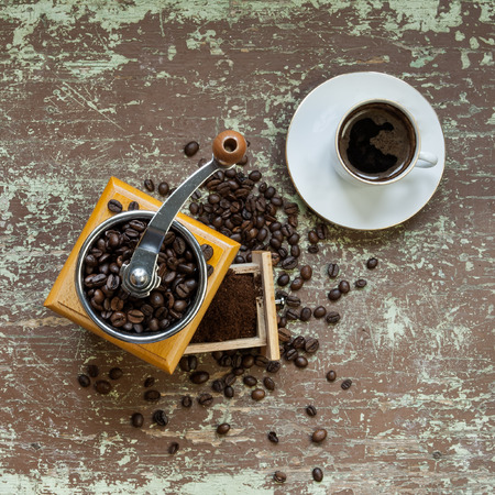 Old coffee grinder and cup of coffee on wooden board Stock Photo